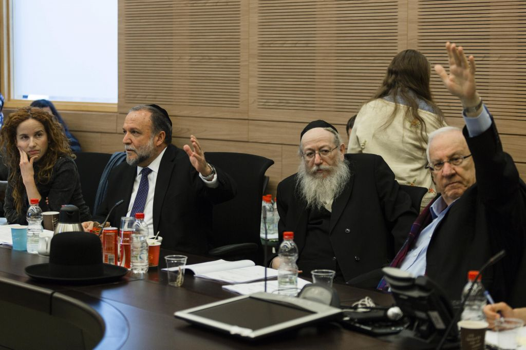 From right, MKs Reuven Rivlin, Yaakov Litsman, Itshak Cohen, and Stav Shaffir, vote during a Finance Committee meeting regarding changes in the budget for 2013, on Tuesday, December 24, 2013. (photo credit: Flash90)