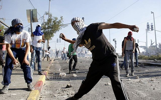 Masked Palestinian protesters throw stones towards Israeli police during clashes in the Shuafat neighborhood in East Jerusalem. July 3, 2014. (photo credit: Sliman Khader/FLASH90)