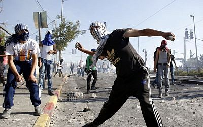 Masked Palestinian protesters throw stones at Israeli police during clashes in the Shuafat neighborhood in East Jerusalem, July 3, 2014 (photo credit: Sliman Khader/Flash90)
