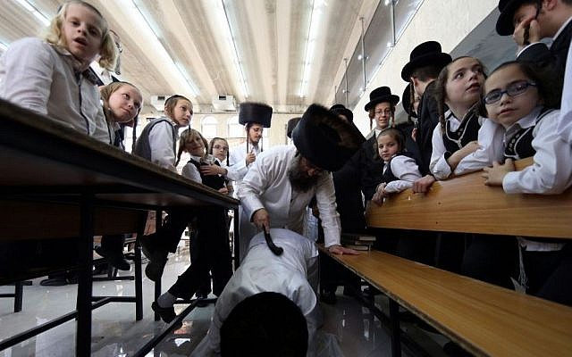 An ultra-Orthodox man of the Hassidic Lelov dynasty whips another with a leather belt as a symbolic punishment for his sins during the traditional 'Malkot' ceremony, a few hours before the start of Yom Kippur, the Day of Atonement, in a synagogue in the town of Bet Shemesh, outside of Jerusalem. October 3, 2014. (Photo credit: Nati Shohat / FLASH90)