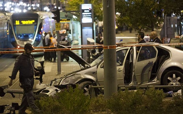 Police and rescue personnel are seen at the scene where several people were injured when a car crashed into the Jerusalem light rail station by Ammunition Hill, October 22, 2014. (photo credit: Yonatan Sindel/Flash90)