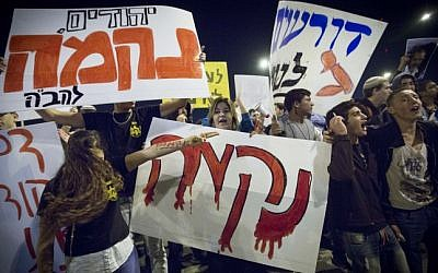 """Right-wing activists carrying signs reading """"Revenge"""" and """"Death to Terrorists"""" protest at the site where a young Palestinian man rammed his car into pedestrians waiting for the light rail in Jerusalem, October 23, 2014 (Photo credit: Miriam Alster/Flash90)"""