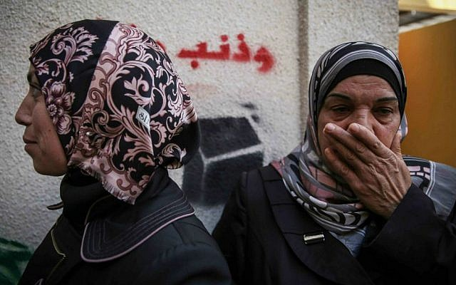 Family members seen taking shelter from tear gas while mourning at the home of the Palestinian man from the East Jerusalem neighborhood of Abu Tor suspected of the attempted murder of Yehudah Glick, October 30, 2014. (Hadas Parush/ Flash90)