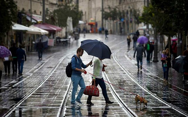 Israelis hold umbrellas to protect themselves from the rain as they walk on Jaffa Street, downtown Jerusalem, October 31, 2014. (Miriam Alster/Flash90)