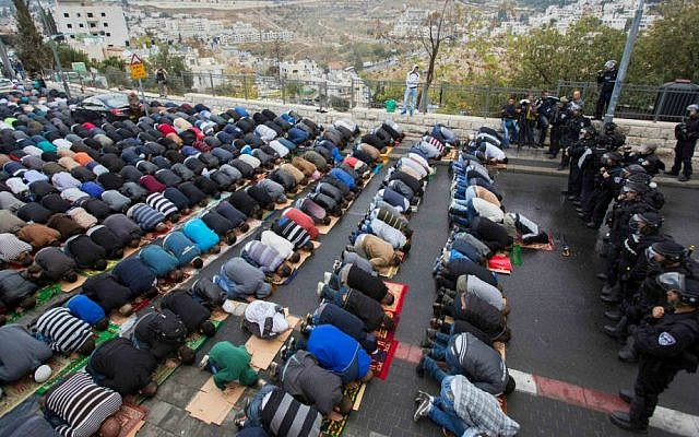 Young Palestinian men, who were prevented by Israeli police from praying at the Temple Mount as a measure intended to head off escalating violence, pray at the police cordon in the East Jerusalem neighborhood of Wadi al-Joz, October 31, 2014. (Yonatan Sindel/Flash90)