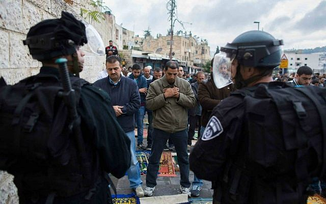 Palestinians prevented from reaching the Temple Mount on Friday pray at the police cordon in the East Jerusalem neighborhood of Wadi Joz, October 31, 2014. (Yonatan Sindel/Flash90)