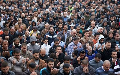 Palestinians pray as Israeli policemen guard (unseen) during Friday prayers in the East Jerusalem neighborhood of Wadi Joz, October 31, 2014. (Yonatan Sindel/Flash90)