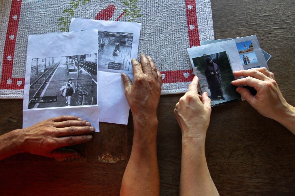 In this Thursday, Oct. 2, 2014 photo, Kamel Ali Mehenni, left, and his wife, Severine, hold pictures of their daughter Sahra at their home in Lezignan Corbieres, France. At left is a frame grab taken from a security camera showing Sahra at the Carcassonne railway station on March 11, 2014, the day she left her home on her way to Syria. (photo credit: AP Photo/ Fred Scheiber)
