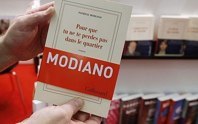 A man holds a book of French author Patrick Modiano at the Book Fair in Frankfurt, Germany, Thursday, Oct. 9, 2014. Modiano won this year's nobel prize for literature. (photo credit: AP Photo/Michael Probst)
