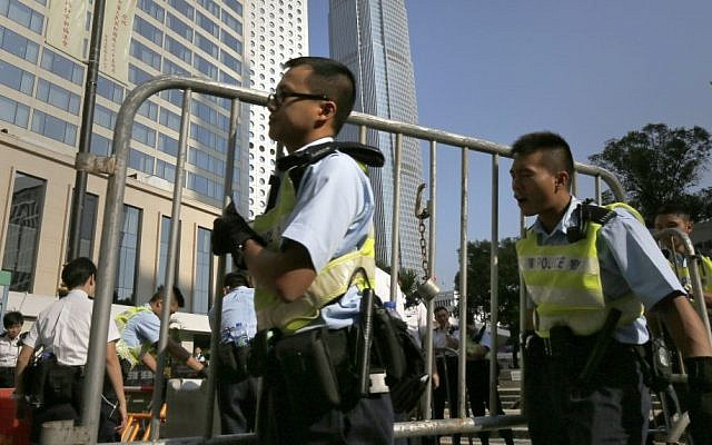 Police officers remove some barricades used by pro-democracy protesters who have been occupying main roads in the Asian financial center for two weeks in Hong Kong, Monday, Oct. 13, 2014. (photo credit: AP/Vincent Yu)