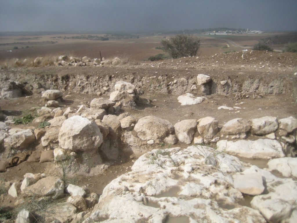 The bedrock floor and wall of the Late Bronze Age courtyard at Tel Burna, with Kibbutz Beit Nir in the background. (photo credit: Ilan Ben Zion/Times of Israel staff)