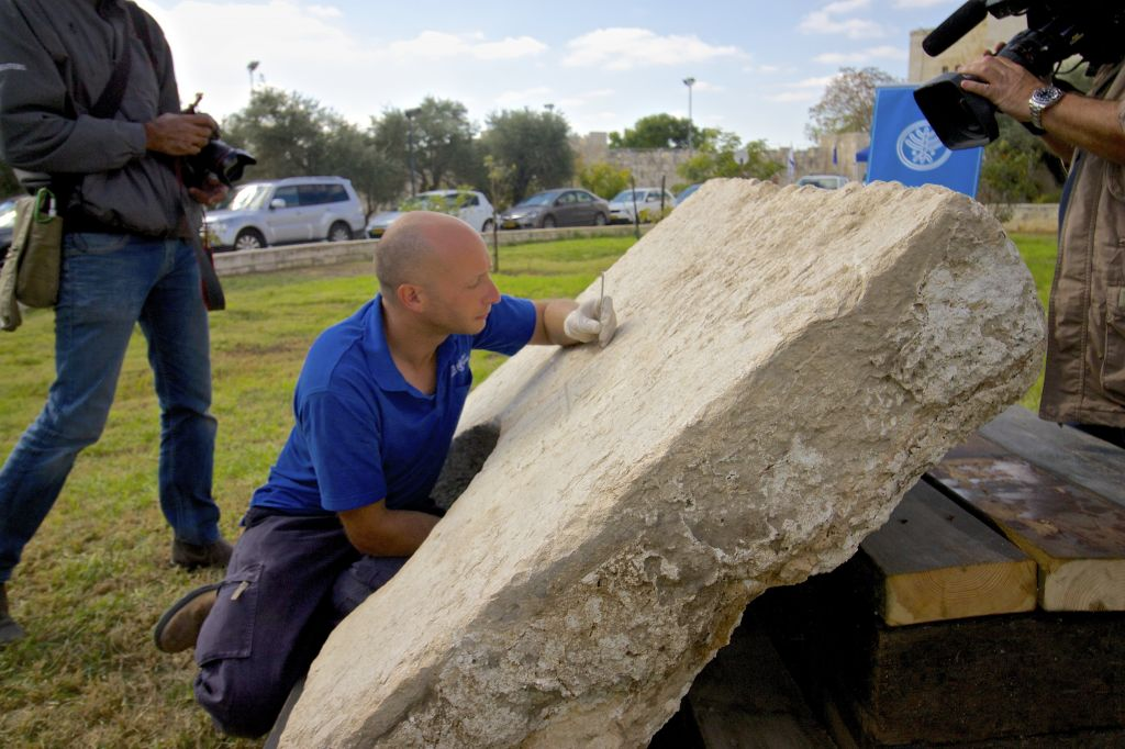 Roie Greenwald attends to a Roman inscription found in Jerusalem (photo credit: Moti Tufeld)