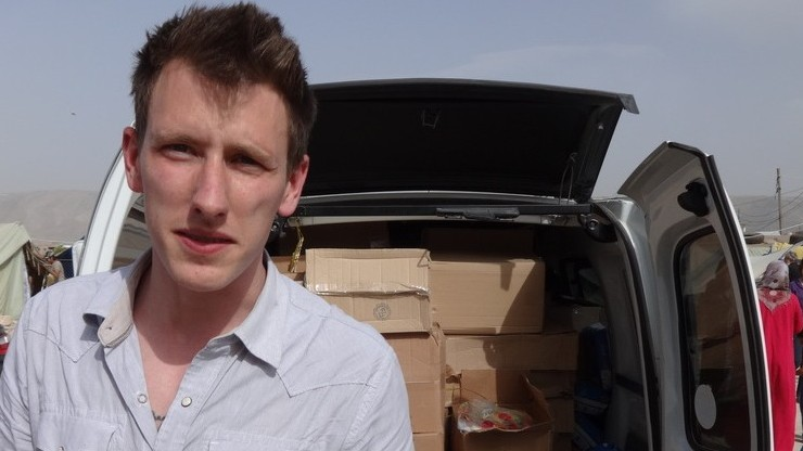 Peter Kassig standing in front of a truck filled with supplies for Syrian refugees. A video produced by militants in Syria released Friday, Oct. 3, 2014, shows Kassig, of Indianapolis, kneeling on the ground as a masked militant says he will be killed next. (photo credit: AP Photo/Courtesy Kassig Family)