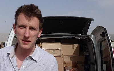 This undated photo provided by the Kassig family shows Peter Kassig standing in front of a truck filled with supplies for Syrian refugees. (photo credit: AP/Courtesy Kassig Family)