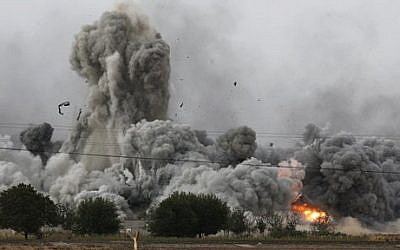 Thick smoke, debris and fire rise following an airstrike by the US-led coalition in Kobani, Syria, as fighting intensified between Syrian Kurds and the militants of Islamic State group, as seen from Mursitpinar on the outskirts of Suruc, at the Turkey-Syria border, Sunday, Oct. 12, 2014. (photo credit: AP Photo/Lefteris Pitarakis)