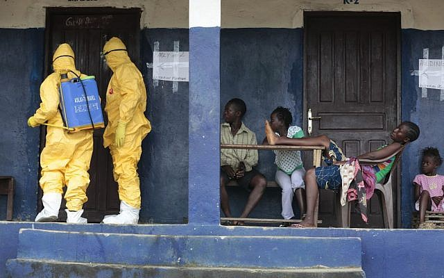 Illustrative photo of health officials disinfecting a room that had been inhabited by suspected Ebola in Liberia, on September 30, 2014. (photo credit: AP/Jerome Delay, File)