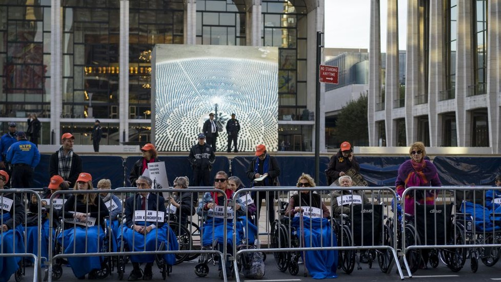 People, some in wheelchairs, gather at Lincoln Center, with the Metropolitan Opera House in the background, as they protest 'Death of Klinghoffer' Monday, Oct 20, 2014, in New York. (Photo credit: AP/Craig Ruttle)