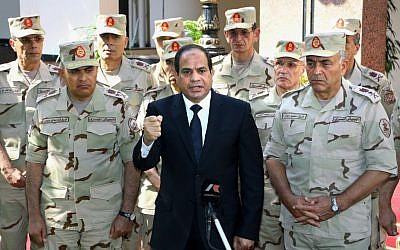Egyptian President Abdel-Fattah el-Sissi, center, speaks in front of the state-run TV ahead of a military funeral for 30 troops killed in an assault in the Sinai Peninsula, as he stands with army commanders in Cairo, Egypt, Saturday, Oct. 25, 2014 (photo credit: AP/MENA)