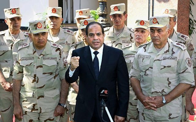File: Egyptian President Abdel-Fattah el-Sissi, center, speaks in front of the state-run TV ahead of a military funeral for 30 troops killed in an assault in the Sinai Peninsula, as he stands with army commanders in Cairo, Egypt, Saturday, Oct. 25, 2014 (AP/MENA)