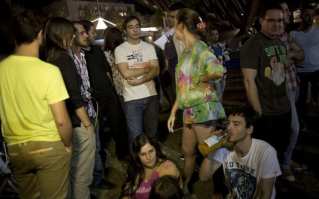 In this photo taken Tuesday, Oct. 14, 2014, Israelis attend a gathering encouraging others to immigrate to Berlin in Tel Aviv, Israel. A group of young Israeli expats have unleashed a storm of controversy back home by encouraging others to join them in Berlin, touching on two of the most sensitive issues in Israel: the country's high cost of living and Jews' tortured history with Germany. (photo credit: AP Photo/Ariel Schalit)