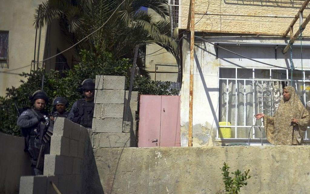 In this photo taken Tuesday, Sept. 30, 2014, a Palestinian woman stands in front of her Silwan apartment while Israeli police officers secure an alleyway leading to the entrance of a home that Jewish settlers had moved into. (AP Photo/Mahmoud Illean)