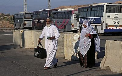 Palestinian pilgrims cross the Beit Hanoun checkpoint on their way to the Erez border crossing between Israel and Gaza and then to Jerusalem, during the three-day Muslim holiday of Eid al-Adha, in the northern Gaza Strip, Sunday, Oct. 5, 2014. (photo credit: AP/Adel Hana)