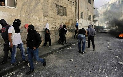Palestinian youths throw stones during clashes with border police in East Jerusalem, Thursday, Oct. 30, 2014. (AP Photo/Mahmoud Illean)