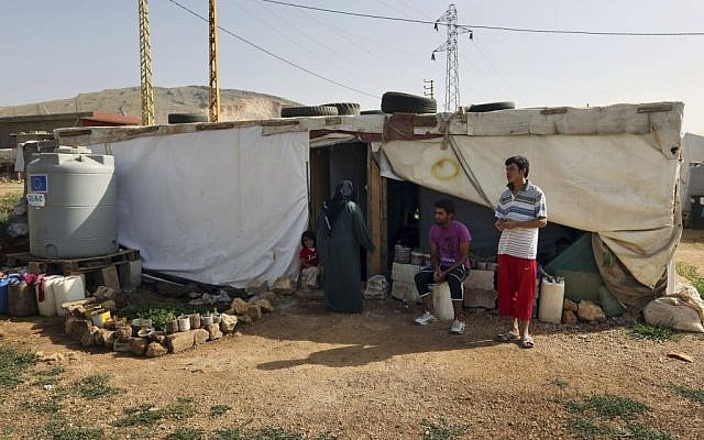 Syrian refugees stand outside their tent at a Syrian refugee camp in the eastern Lebanese town of Majdal Anjar, Lebanon. The Lebanese government said Thursday, October 23, that the tiny Mediterranean country will not accept any more Syrian refugees except for what authorities deem to be 'exceptional' cases. (photo credit: AP/Bilal Hussein)