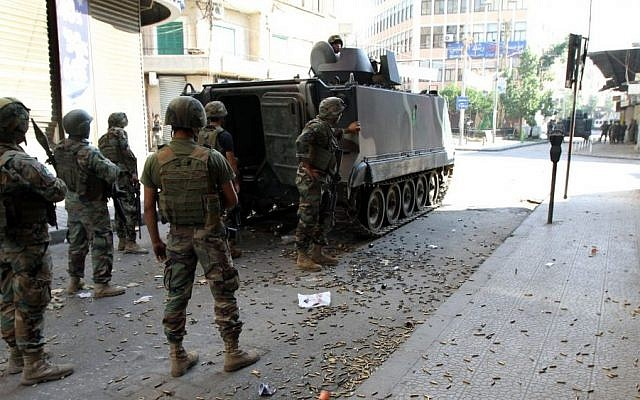 Lebanese Army soldiers stand beside an armored vehicle during clashes with Islamic militants, in the northern port city of Tripoli, Lebanon, on Saturday, October 25, 2014. (photo credit: AP)