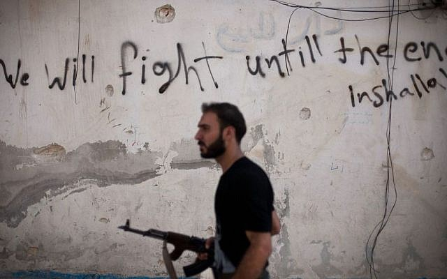A Free Syrian Army fighter walks through a street in the Amariya district of Aleppo, Syria, on September 10, 2012. (photo credit: AP/Manu Brabo, File)