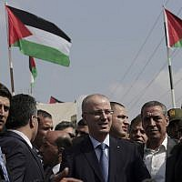 Palestinian Authority Prime Minister Rami Hamdallah (center), arrives at the Palestinian side of the Beit Hanoun border crossing in the northern Gaza Strip, Thursday, October 9, 2014. (photo credit: AP/Adel Hana)