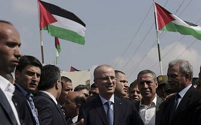 Palestinian Authority Prime Minister Rami Hamdallah, center, arrives at the Palestinian side of the Beit Hanoun border crossing in the northern Gaza Strip, Thursday, Oct. 9, 2014. Members of the new Palestinian unity government assembled in Gaza on Thursday for their first Cabinet session in the war-battered territory - a largely symbolic meeting meant to mark the end of absolute Hamas control of the coastal strip. (photo credit: AP Photo/Adel Hana)