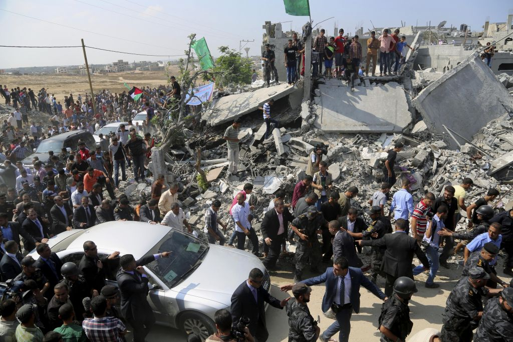 Members of the Palestinian Authority security forces gather around the car carrying Prime Minister Rami Hamdallah on a tour to destroyed houses in an area east of the Beit Hanoun border crossing in the northern Gaza Strip, Thursday, Oct. 9, 2014. (photo credit: AP Photo/Adel Hana)
