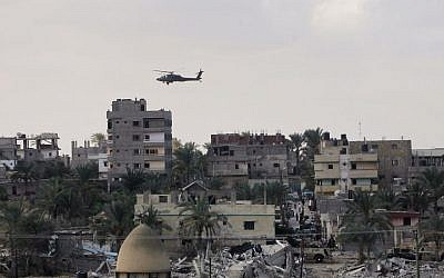 An Egyptian helicopter hovers over houses destroyed by the Egyptian army on the Egyptian side on the border town of Rafah, Wednesday, Oct. 29, 2014. (Photo credit: AP/Eyad Baba)