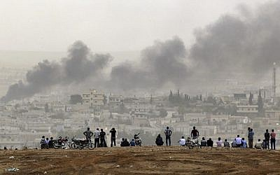 People on a hilltop watch smoke rising from a fire caused by a strike in Kobani, Syria, during fighting between Syrian Kurds and the militants of Islamic State group, on the outskirts of Suruc, at the Turkey-Syria border, on October 11, 2014. (AP Photo/Lefteris Pitarakis, File)