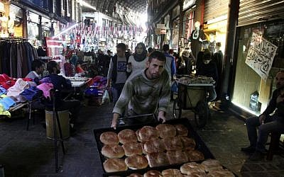A bread seller pushes his wares through the ancient bazaar known as the Hamidiyeh souq in Damascus, Syria, Monday, Oct. 27, 2014. (photo credit: AP/Diaa Hadid)