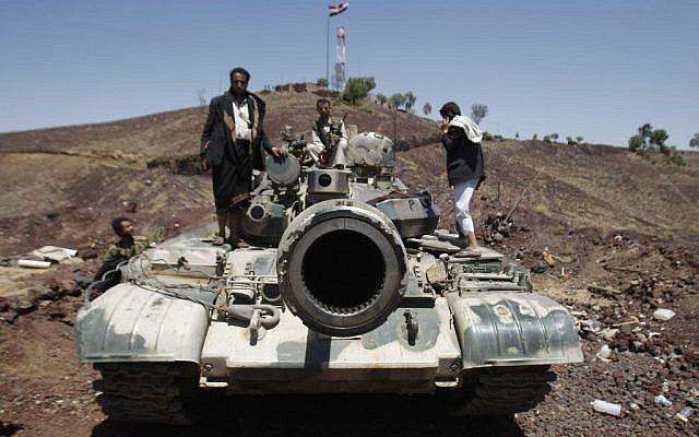 Hawthi Shiite rebels stand on a tank at the compound of the army's First Armored Division, after they had taken it over, in Sanaa, Yemen, Sept. 22, 2014. (photo credit: AP Photo/Hani Mohammed)