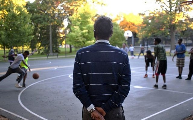 Abdirizak Bihi, executive director of the Somali Education and Social Advocacy Center, watches kids play basketball at Currie Park in Minneapolis, Sept. 22, 2014 (photo credit: AP/Craig Lassig)