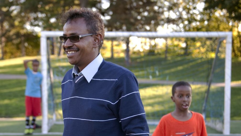 Abdirizak Bihi, executive director of the Somali Education and Social Advocacy Center, spends time with kids playing soccer at Currie Park in Minneapolis, In this Monday, Sept. 22, 2014. (AP Photo/Craig Lassig)