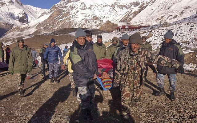 Nepalese Army soldiers carry an avalanche victim before he is airlifted in Thorong La pass area, Nepal, Wednesday, October 15, 2014. (photo credit: AP/Nepalese Army)