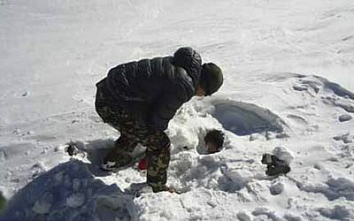 A Nepalese army soldier searches for avalanche victims at Thorong La pass area in Nepal, Sunday, Oct. 19, 2014. Nepalese officials closed a section of a popular Himalayan trekking route Sunday after rescuers, overwhelmed with last week's snowstorms that killed 38 hikers, had to bring to safety new climbers who set out on the same mountain trails where the blizzards struck. (photo credit: AP Photo/Nepalese Army)