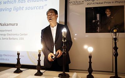 Scientist Shuji Nakamura, a Japanese-born American professor at the University of California, Santa Barbara, demonstrates LED lights during a news conference, Tuesday, Oct. 7, 2014, in Santa Barbara, Calif. Nakamura and two Japanese scientists won the Nobel Prize in physics on Tuesday for inventing blue light-emitting diodes, a breakthrough that has spurred the development of LED technology to light up homes, computer screens and smartphones worldwide. (photo credit: AP/Jae C. Hong)