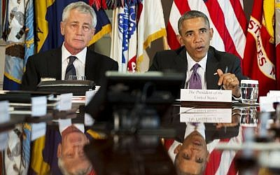 US President Barack Obama sits next to US Defense Secretary Chuck Hagel as he speaks to the media at the conclusion of a meeting with senior military leadership, Wednesday, Oct. 8, 2014, at the Pentagon. (AP Photo/Jacquelyn Martin)