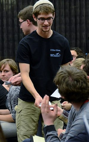 Henry Rosen, a student organizer for the Open Hillel conference at Harvard, handing out material at a plenary session, Oct. 12, 2014. (Gili Getz/JTA)
