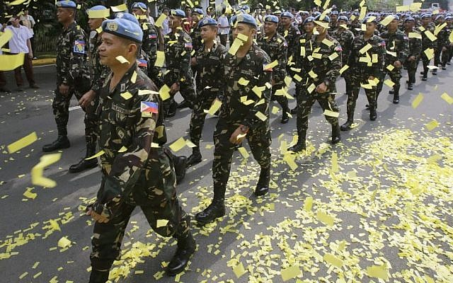 Confetti rains on marching Filipino UN peacekeepers as they are given a hero's welcome Wednesday, Oct. 1, 2014, at Camp Aguinaldo in the Philippines. (photo credit: AP/Bullit Marquez)