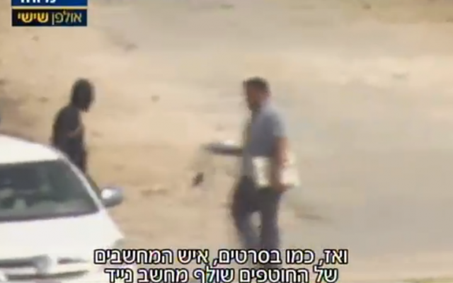 A Nusra Front official carries a laptop to check whether a ransom payment for the release of captured Fijian peacekeepers has gone through, just inside the Syrian border with Israel, September 11, 2014, according to Israel's Channel 2 (Channel 2 screenshot)