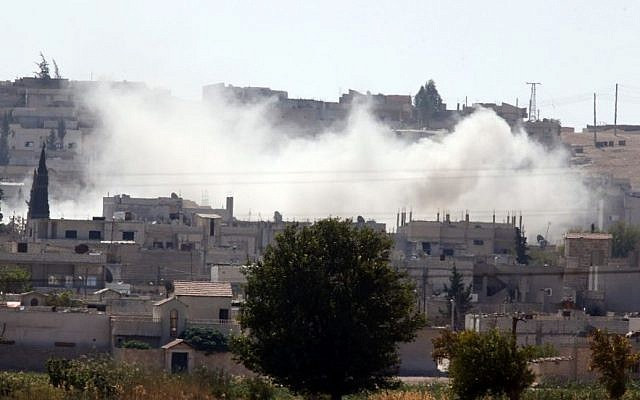 In this image shot from Mursitpinar in the outskirts of Suruc at the Turkey-Syria border, smoke rises from a strike at an area of a mosque that destroyed its minaret, in Kobani, Syria, during heavy fighting between militants with the Islamic State group and Syrian Kurds, Wednesday, Oct. 8, 2014.(Photo credit: AP/Lefteris Pitarakis)