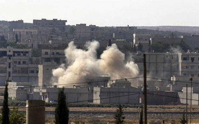 Smoke rises after a shell landed in Kobani in Syria as fighting intensified between Syrian Kurds and the militants of Islamic State group, as seen from Mursitpinar near Suruc, at the Turkey-Syria border, Sunday, October 5, 2014. (photo credit: AP Photo/Lefteris Pitarakis)