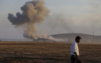 A Turkish Kurd walks away as airstrikes hit Kobani, inside Syria, as fighting intensifies between Syrian Kurds and the militants of Islamic State group, in Mursitpinar, on the outskirts of Suruc, at the Turkey-Syria border, Wednesday, Oct. 8, 2014. (Photo credit: AP/Lefteris Pitarakis)