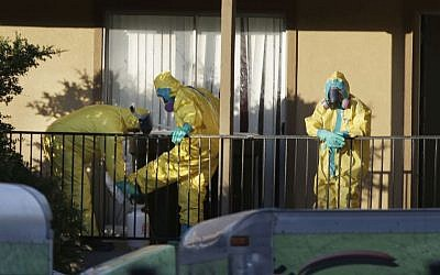 In this Oct. 5, 2014 file photo, hazardous material cleaners disinfectant their personal protective equipment after working in the apartment where Thomas Eric Duncan, the Ebola patient who traveled from Liberia to Dallas, stayed in Dallas. (Photo credit: AP/LM Otero, File)